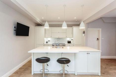 White kitchen with breakfast bar on the island and 2 stools. Behind this are tall housings, wall units and range cooker.