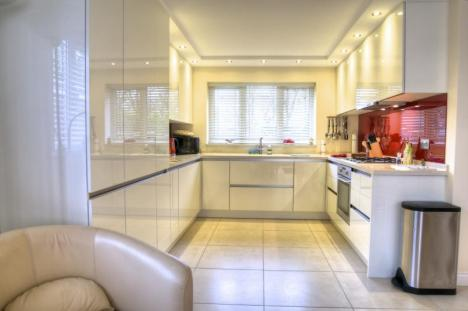 high gloss white handleless fitted kitchen with red glass spalshbacks