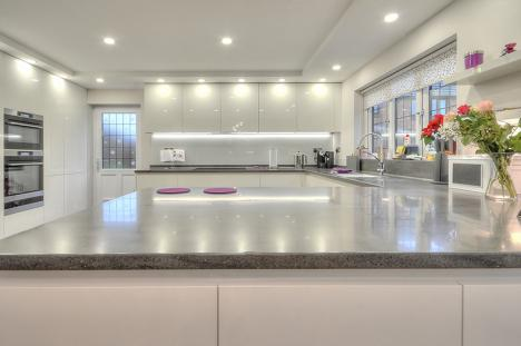 Handleless Keller kitchen in gloss white with Corian® Lava Rock worktops