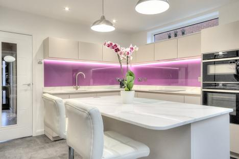 View of white high gloss handleless kitchen with quartzstone worktops