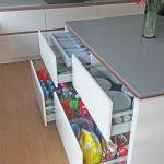 Kitchen island drawers open, showing convenient storage for cutlery, plates and groceries