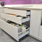 View of white high gloss handleless kitchen with quartzstone worktops and pink glass splashbacks, showing open drawers