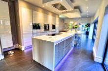 new fitted kitchen with Corian worktops and high-gloss kitchen island with Quooker hot tap