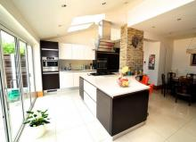 handleless fitted kitchen with Corian tops and Kuppersbusch appliances-