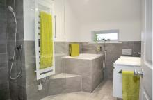 bathroom with half height grey porcelain tiles, towel radiator, deep soaking tub with step up and grab handles, vanity unit
